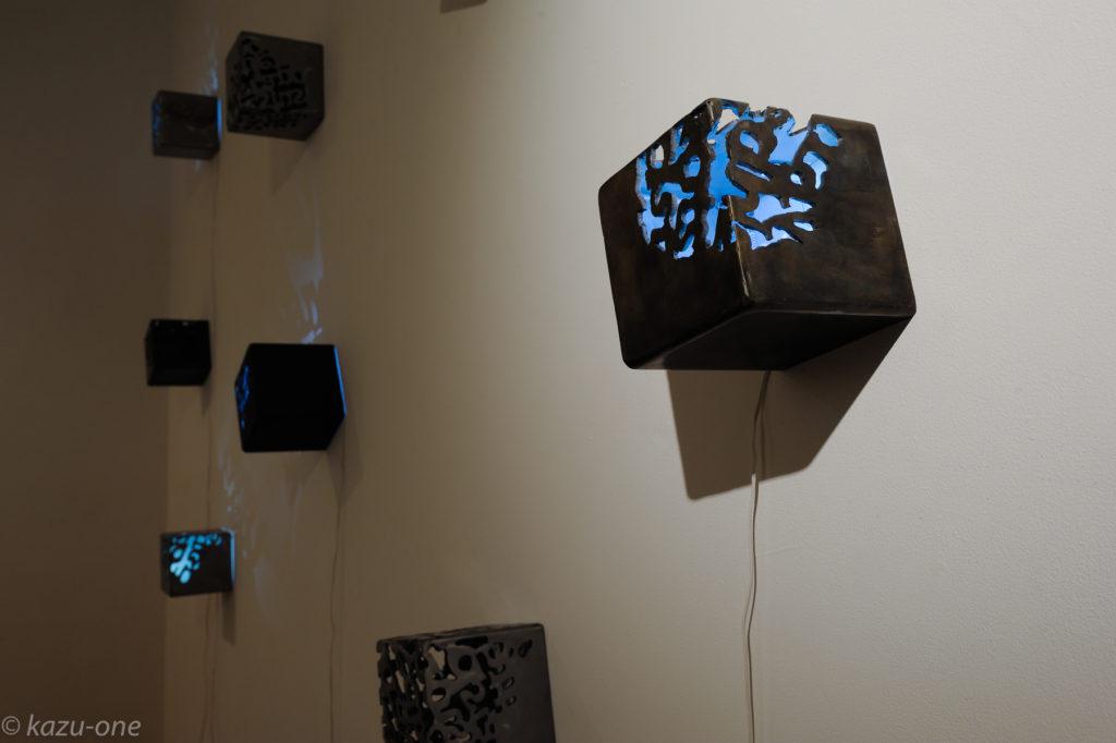 「moonlight/shadow」 / 125mm角 / 素材:鉄,LED,洋箔 球の作品の影の形を一部鉄のキューブへ写し取り切り抜いたもの、球の作品と対になる。 photo by Ikuko HIrose